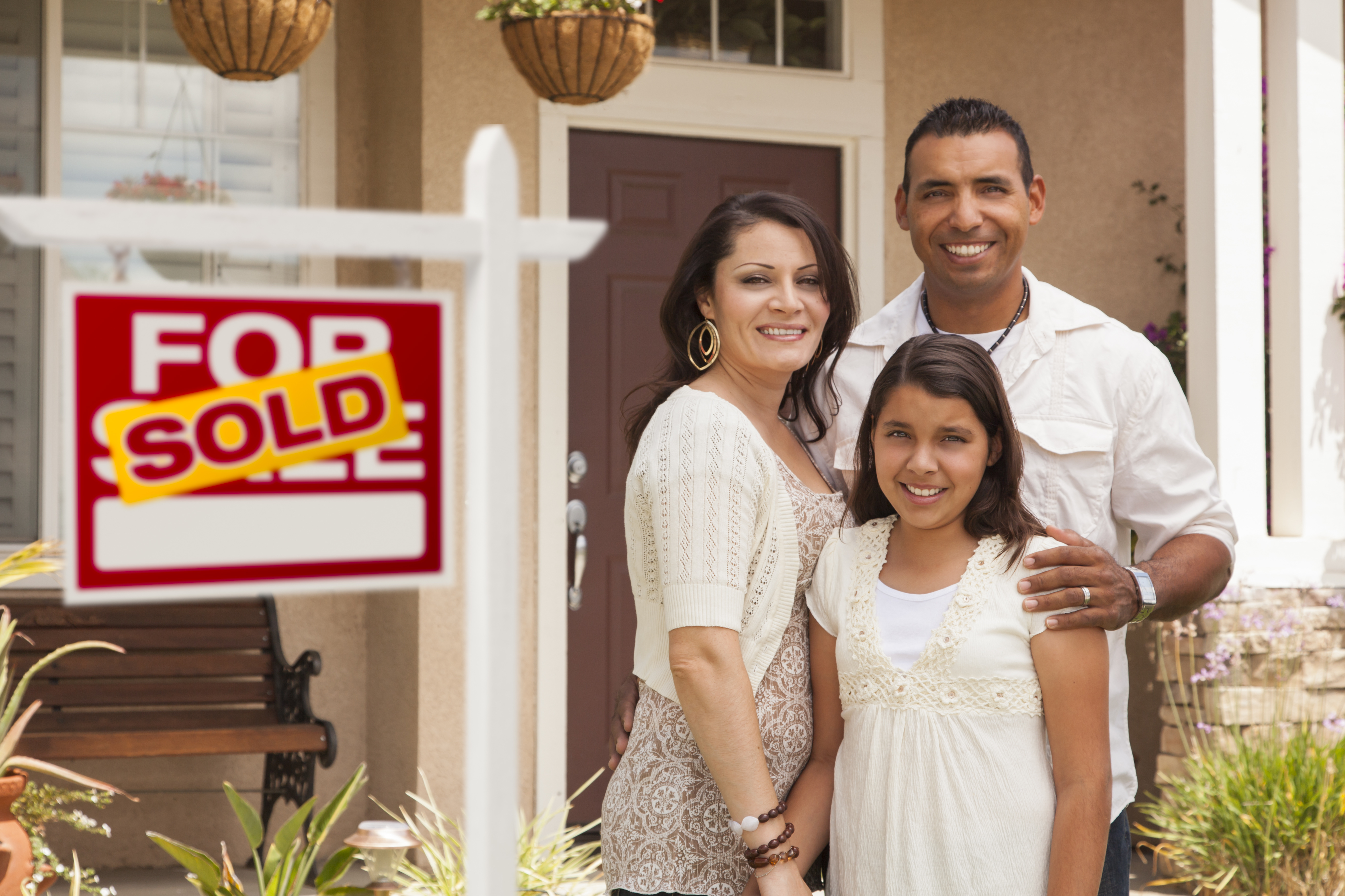 Hispanic Family in Front of Their New Home with Sold Sign