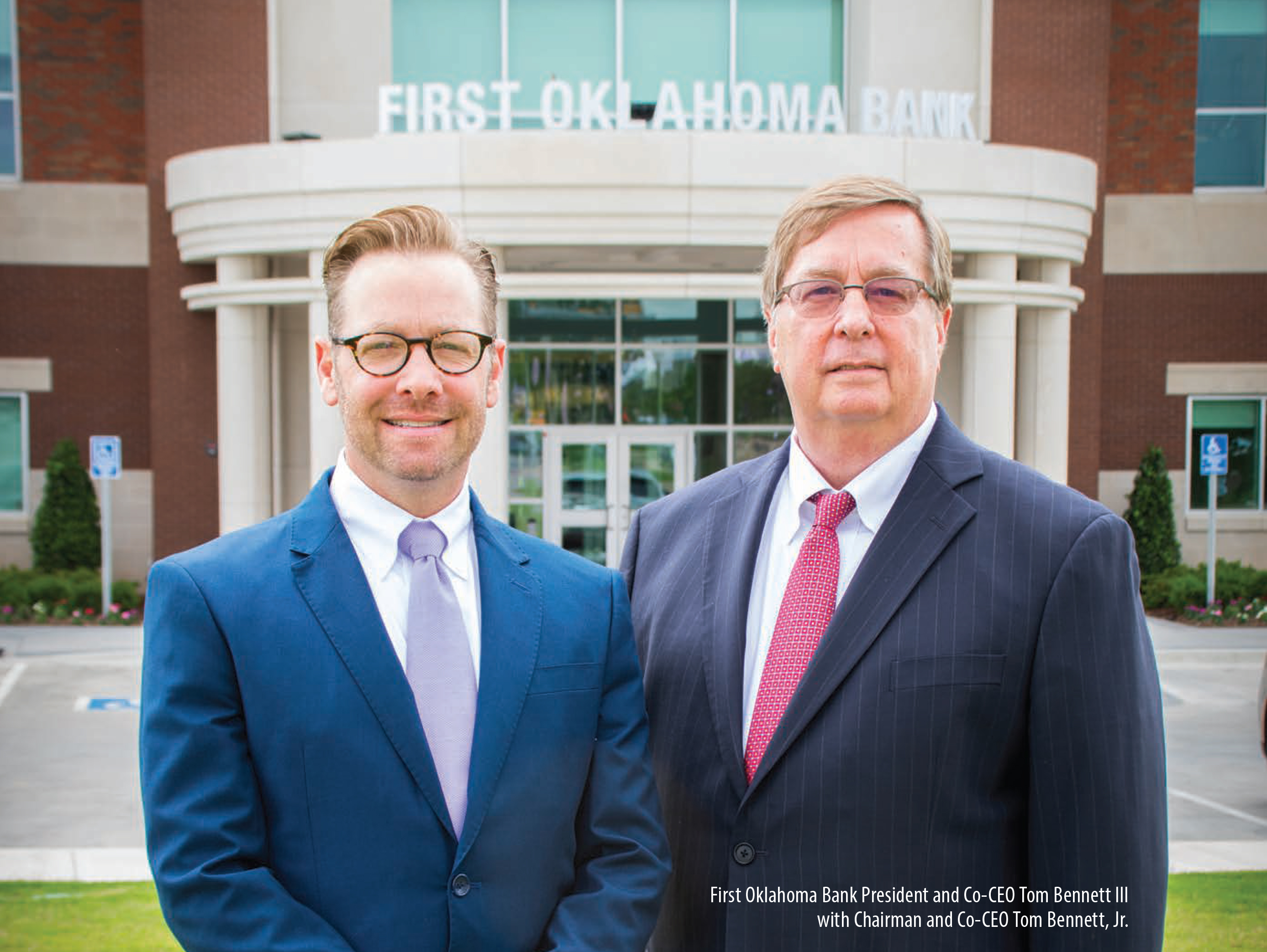 Two men in blue business suits with glasses in front of a building with the words first oklahoma bank.
